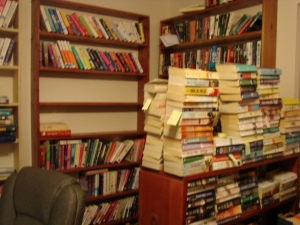 Piles of books are authors that we have 4 or more and eaiser to keep stacked and others on shelves